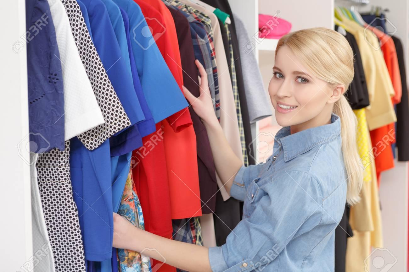 fbadd370fb Foto de archivo - Las últimas tendencias de moda. Mujer rubia hermosa joven  que elige la ropa en una boutique de moda