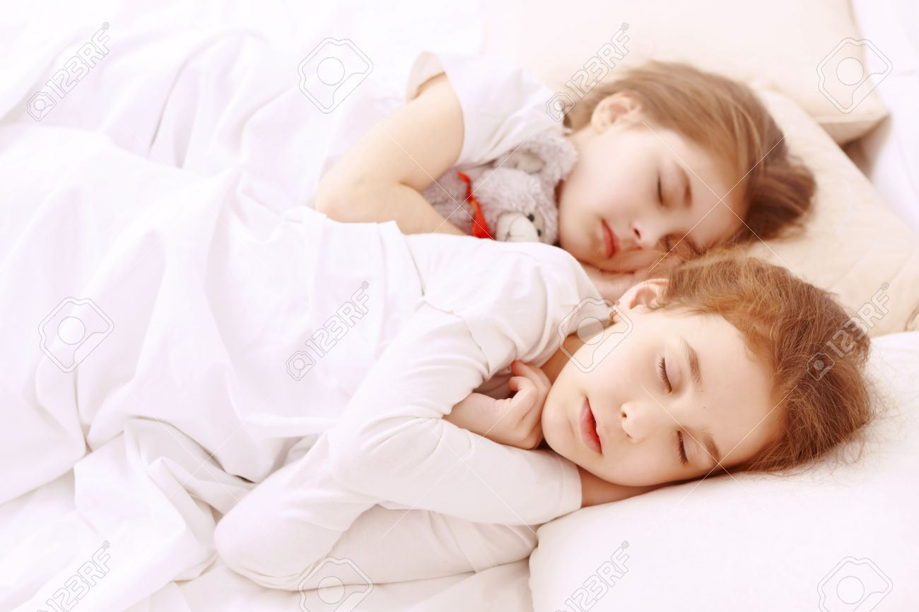 Baby bed next to bed - Two Little Cute Girls Lying Next To Each Other On White Bed And