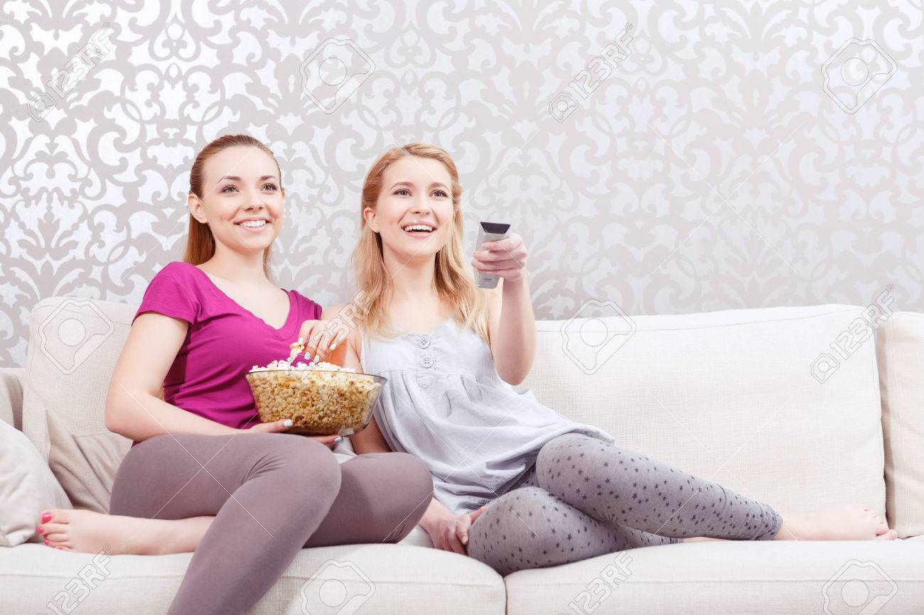 Groovy Movie Night Two Young Beautiful Girls Sitting On A White Couch Squirreltailoven Fun Painted Chair Ideas Images Squirreltailovenorg