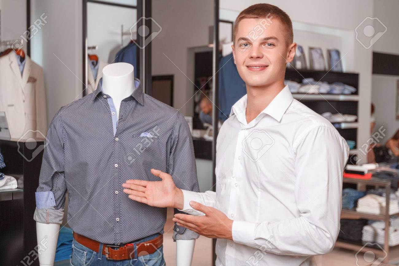 young attractive s assistant demonstrating clothes in his stock photo young attractive s assistant demonstrating clothes in his shop