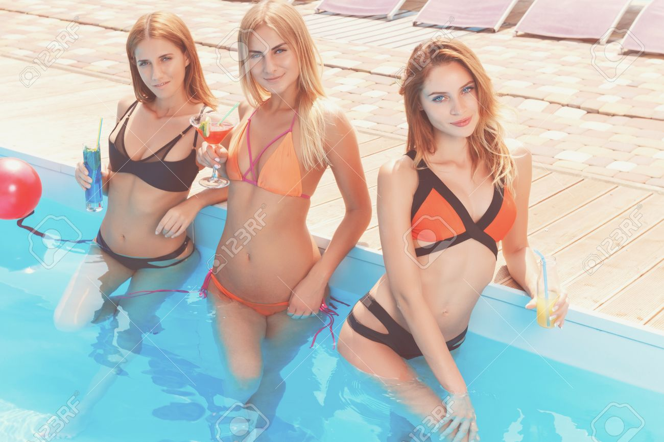 Three sexy pretty girlfriends standing in pool with cocktails during their  summer vacation.