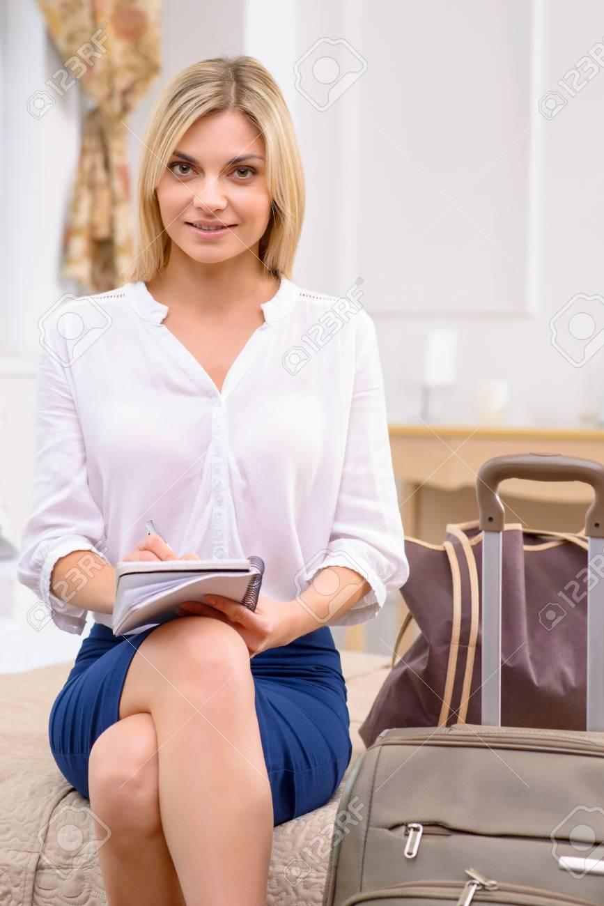 Faire Une Belle Chambre faire la liste. belle jeune femme assise au bord du lit dans sa chambre  d'hôtel et écrit une liste.