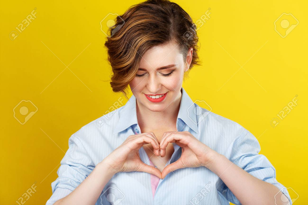 In my heart. Beautiful smiling woman is making a love gesture with her hands and looking happy. - 53157216