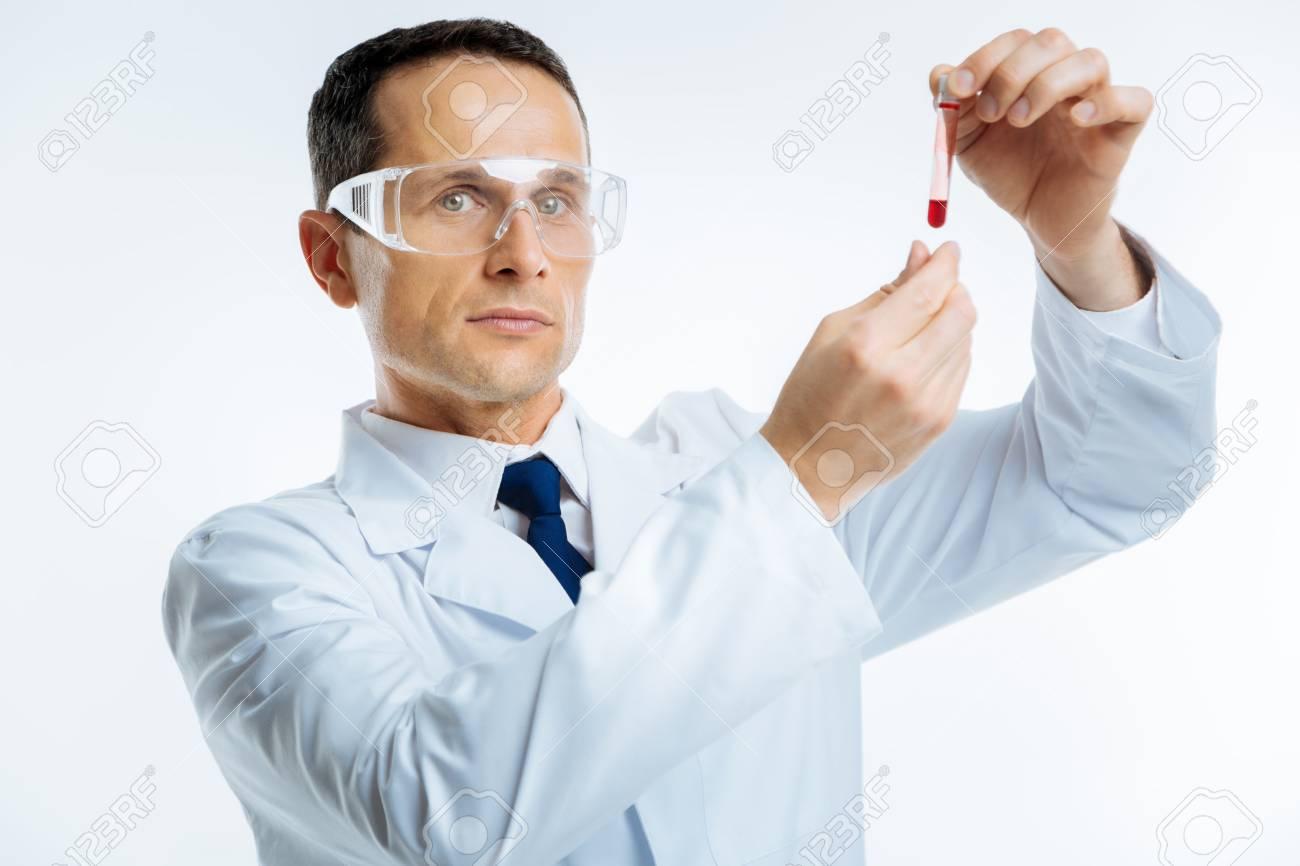 カメラに探している血液サンプルの深刻な医学者 の写真素材・画像素材 ...