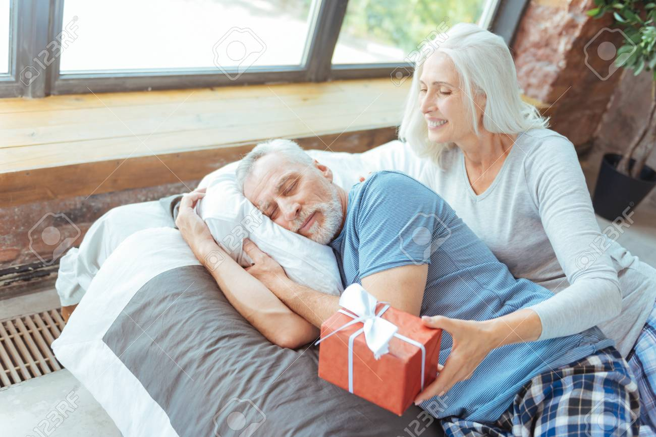 Loving Aged Woman Preparing A Birthday Present For Her Husband Stock Photo