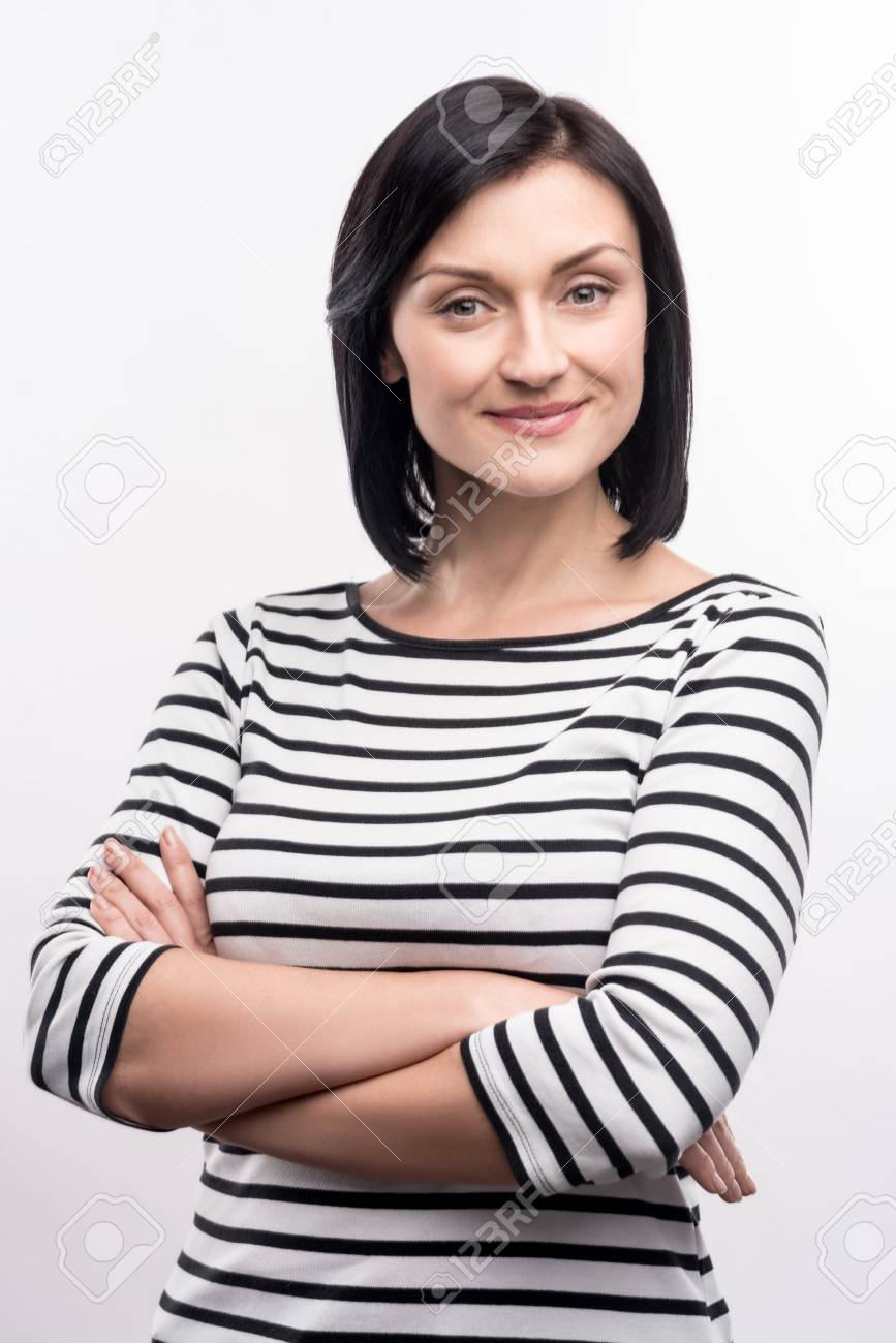 3521ea8c6b5 Natural beauty. Pleasant pretty woman in a striped pullover folding her  hands across her chest