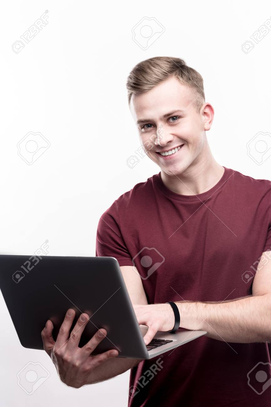 Enjoying work  Upbeat young man in a burgundy t-shirt holding