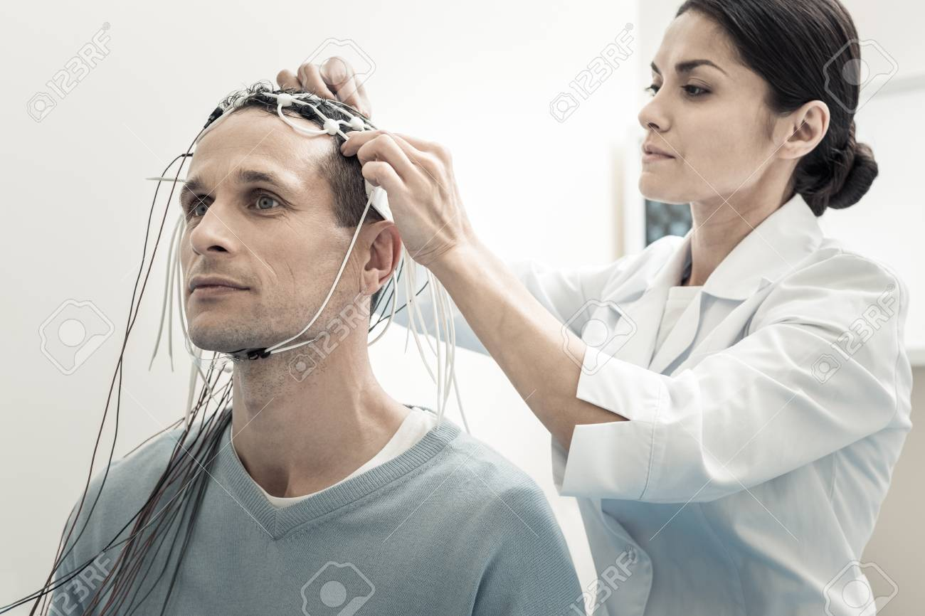 Brain scanning. Professional serious female doctor standing behind her patient and purring electrodes on his head while preparing him for electroencephalogram - 95112105