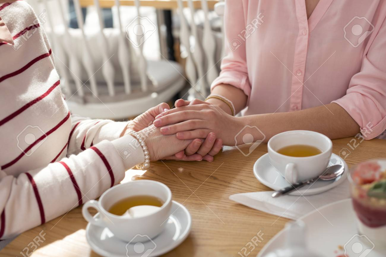 Best granny. Loving caring granddaughter holding hands with her granny while having tea - 100553838