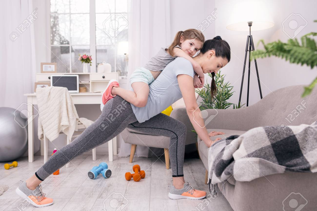 In high spirits. Determined athletic mother training at home and holding her daughter on her back - 100581146