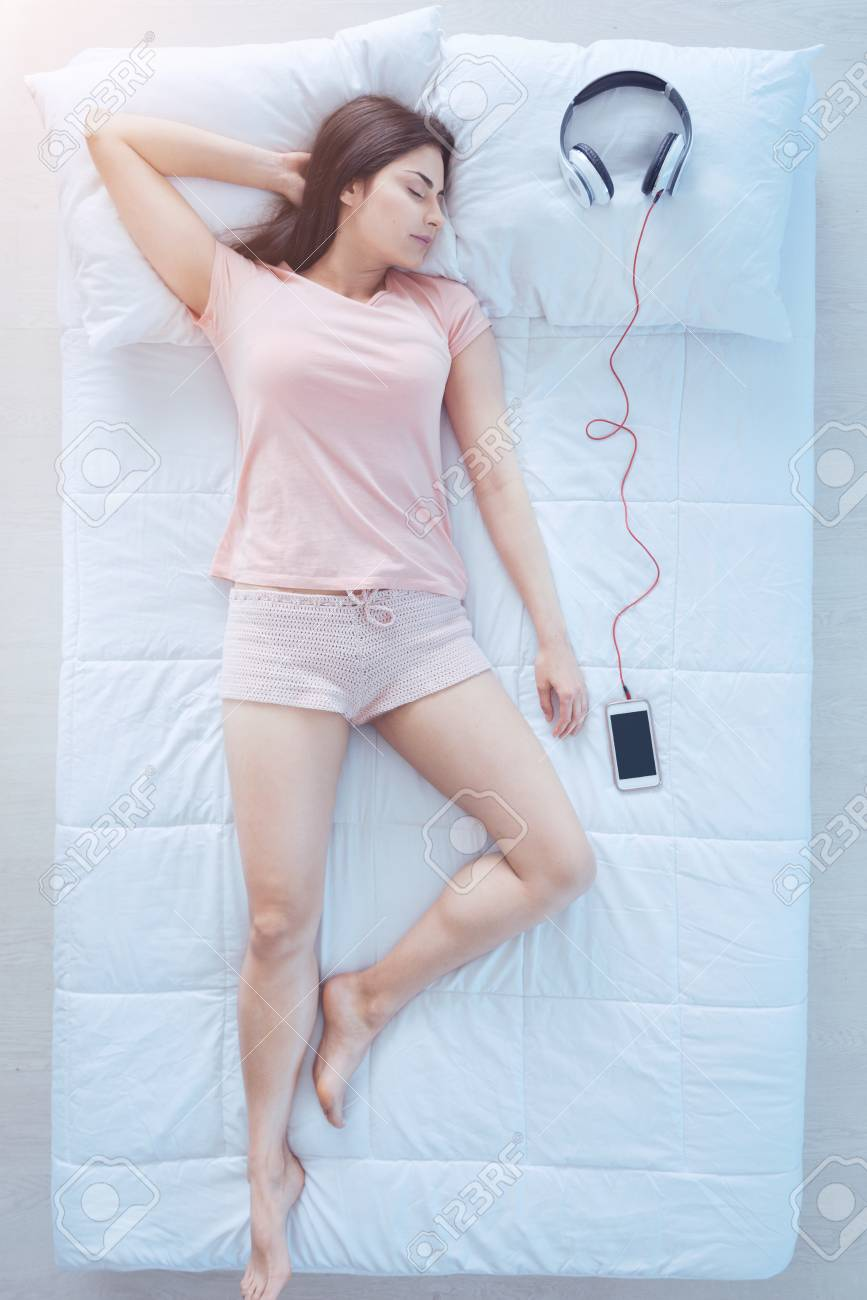 6c6e13660c4eb Completely relaxed. Top view on a young woman wearing pink pajamas lying  next to her