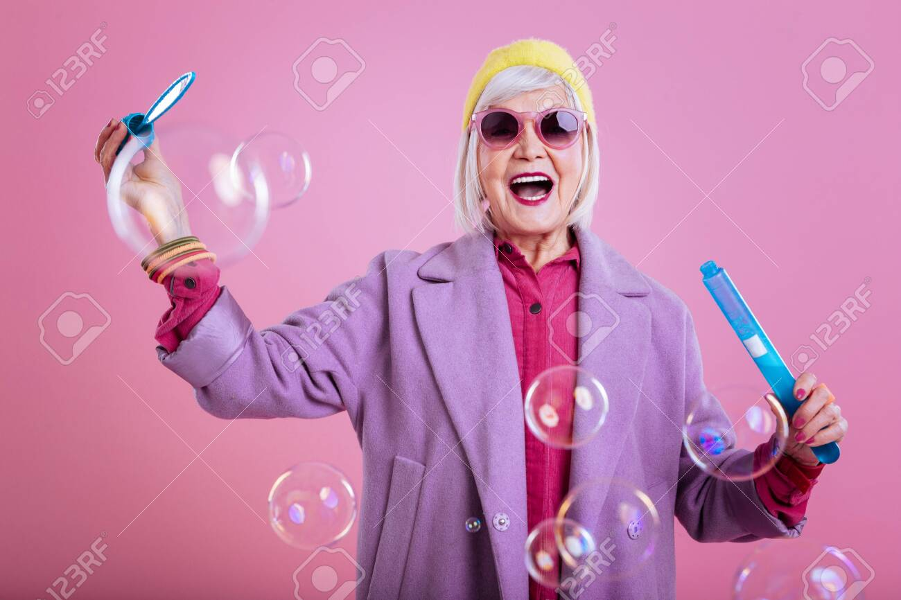 Feeling lovely. Stylish retired woman feeling lovely and cheerful while playing with bubbles - 118456150