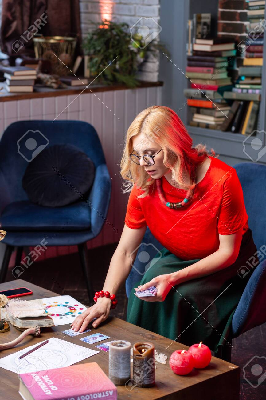 Astrology and cards  Blonde-haired astrologist wearing glasses