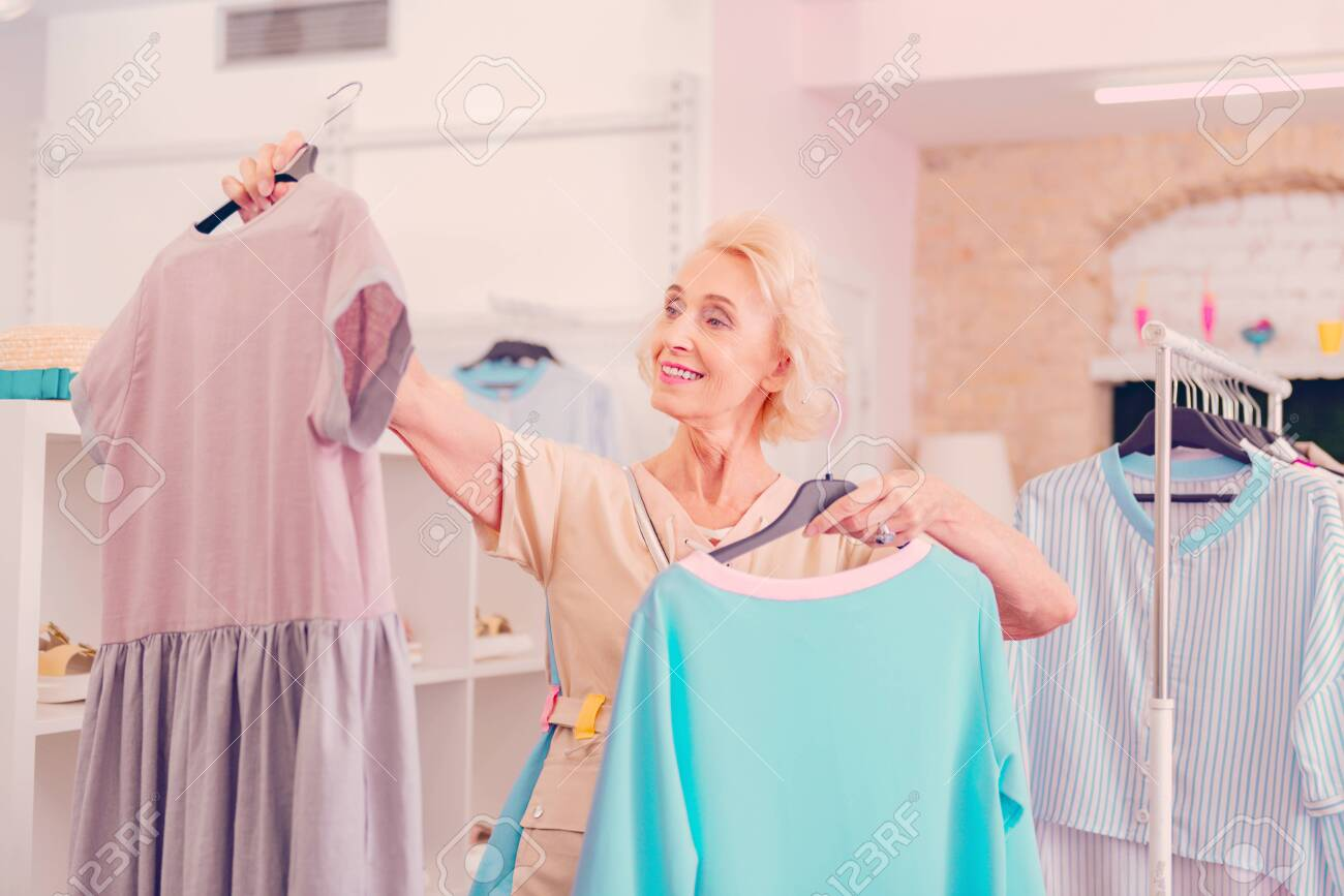 A middle-aged woman choosing among two dresses in the boutique - 120572373
