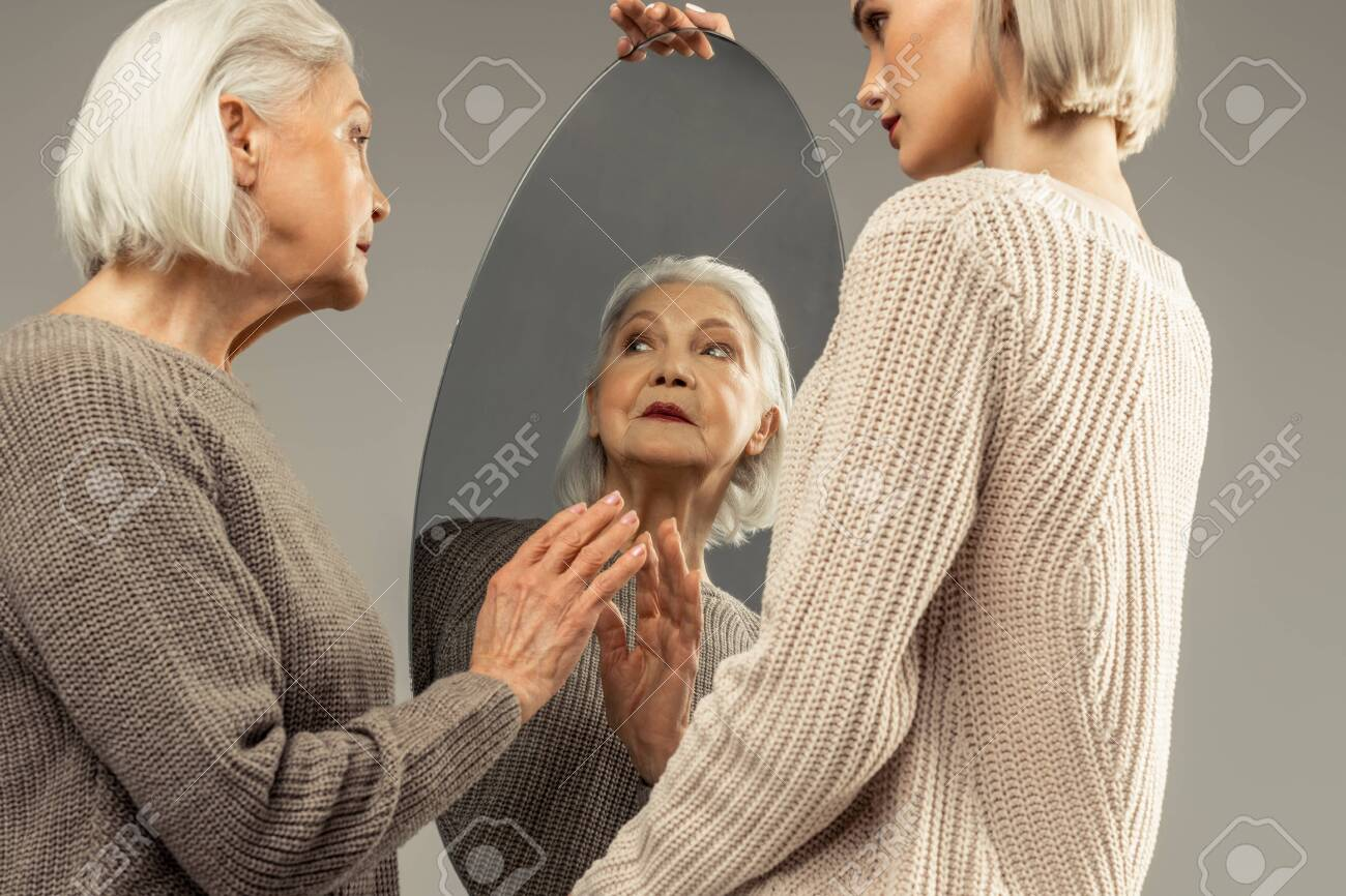 How do I look. Pleasant elderly woman looking at herself while standing in front of the mirror - 120963409