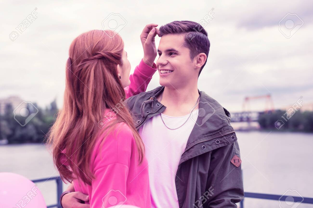 Laughing girlfriend. Lovely long-haired girl correcting hairstyle of her smiling boyfriend while hugging on the coast of the river - 121529925