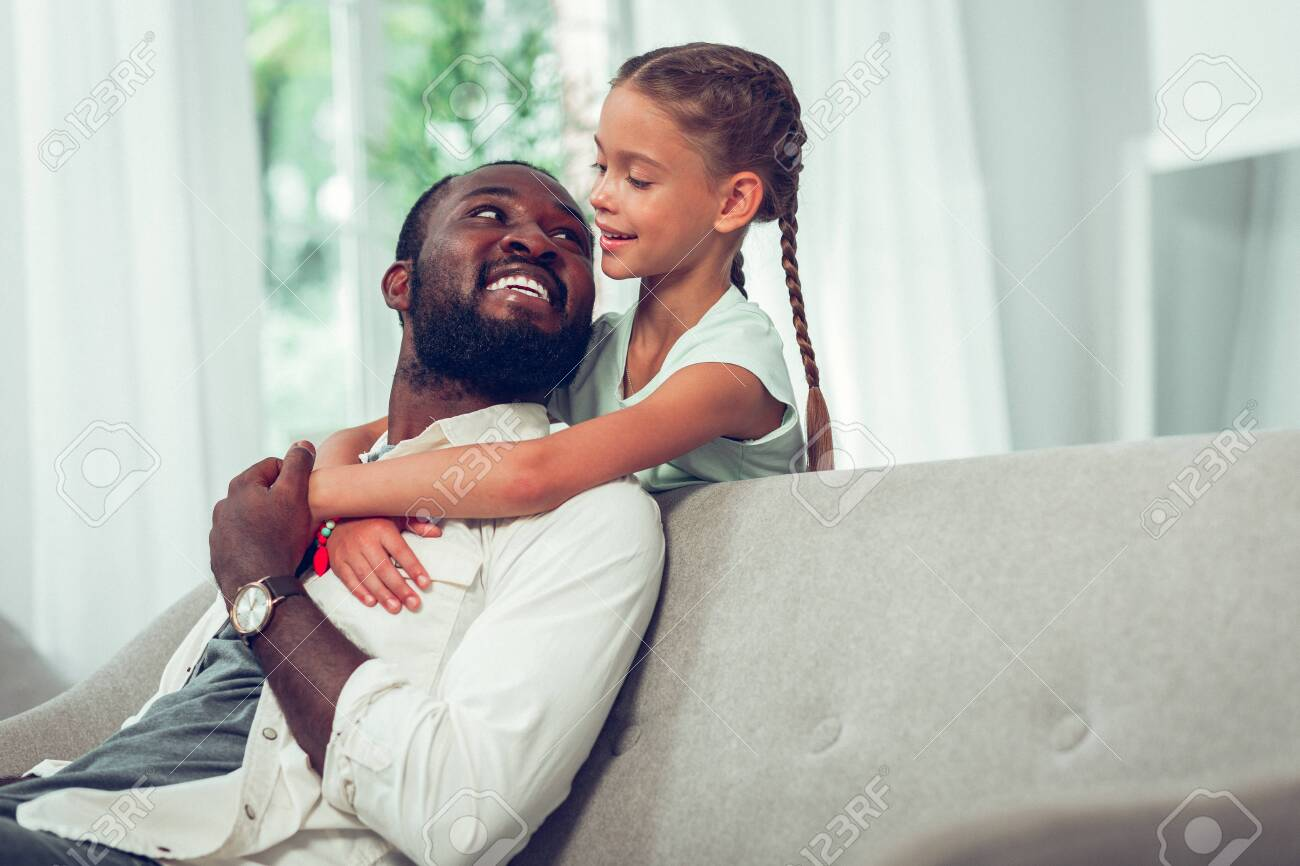 Father and daughter bond. Attractive mid-adult smiling glowing dark-haired bearded Afro-American father lovingly looking at his cute small pretty daughter with long dark braids. - 122667171