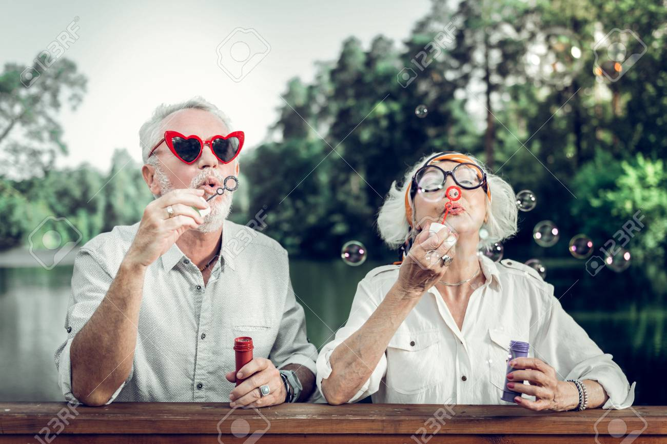 Blowing bubbles. Happy cheerful beaming glowing charming beautiful loving elderly couple in funny sunglasses blowing bubbles outdoors - 124983393