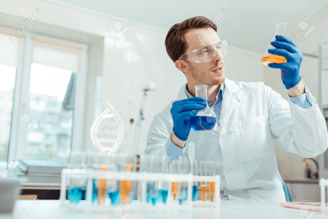 Professional chemist. Nice handsome man holding two different flasks while working in the chemical lab - 127134357