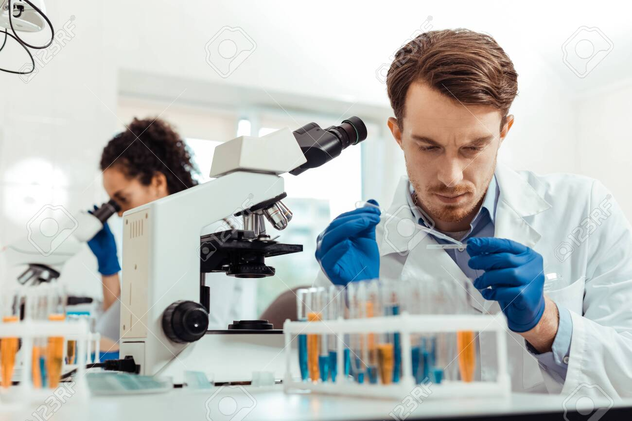 Biological lab. Smart young man being in the lab while working as a biologist - 127134521