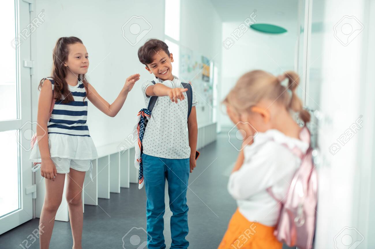 Laughing at girl. Rude boy and girl laughing at little blonde girl standing near lockers - 126754214
