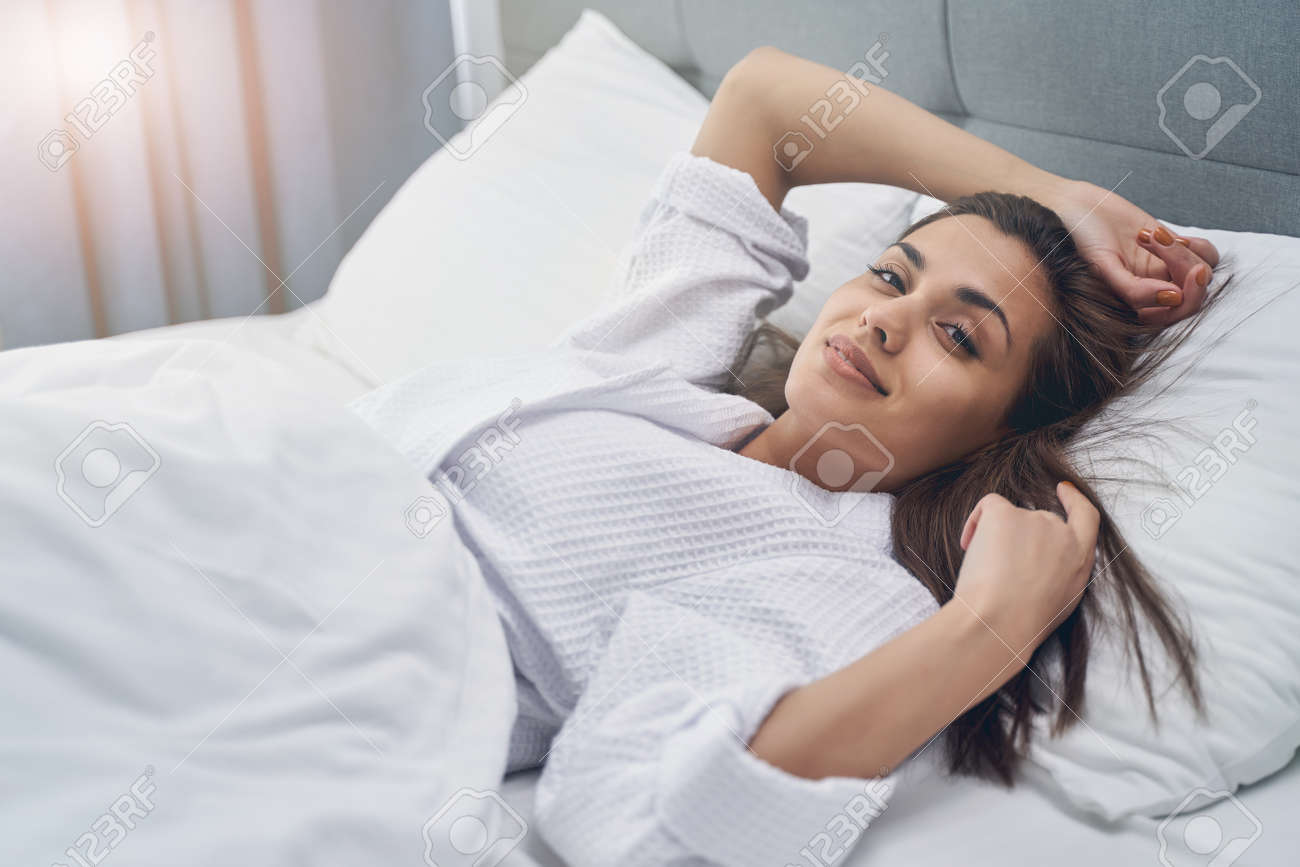 Attractive lady looking at camera and smiling while resting in bedroom - 150137059