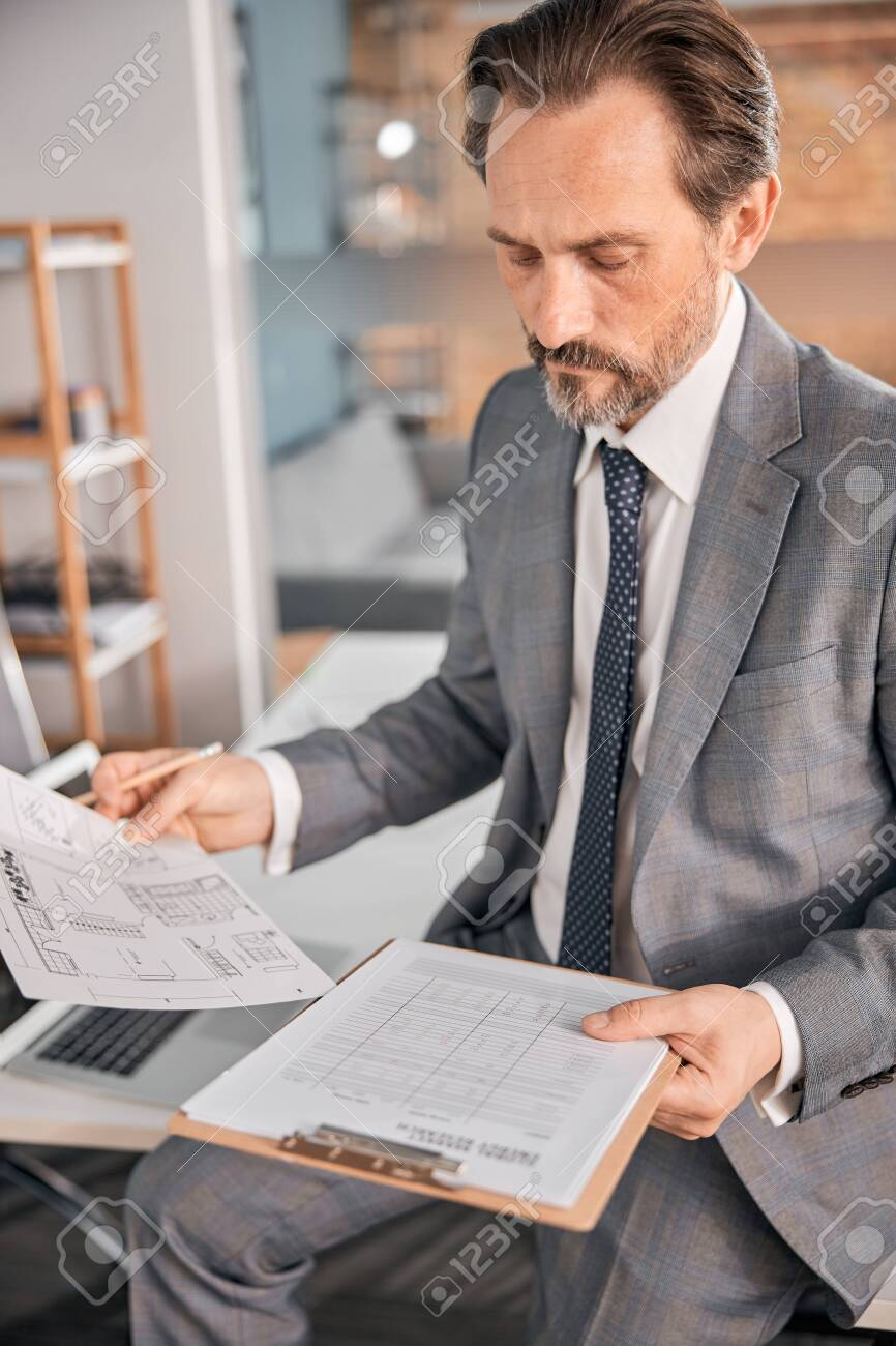 Serious gentleman in stylish suit working with papers while sitting on office table - 152676855