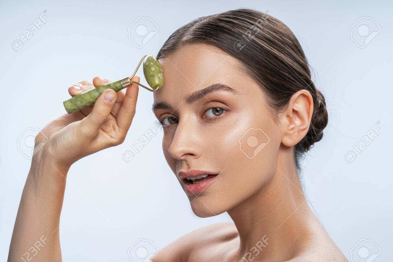 Close up portrait of a pretty lady with a natural jade roller looking at the camera - 154460909