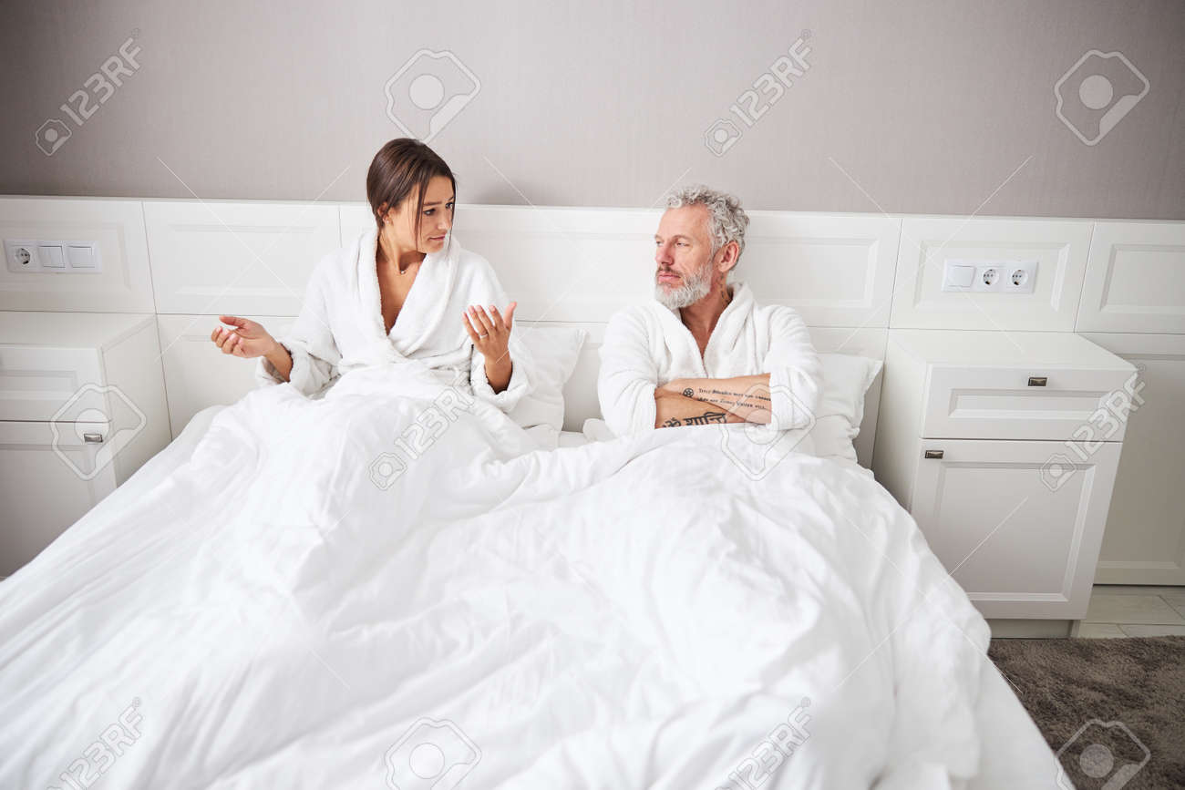 Brunette Caucasian woman looking to her husband while gesturing with both hands in room indoors - 169456670
