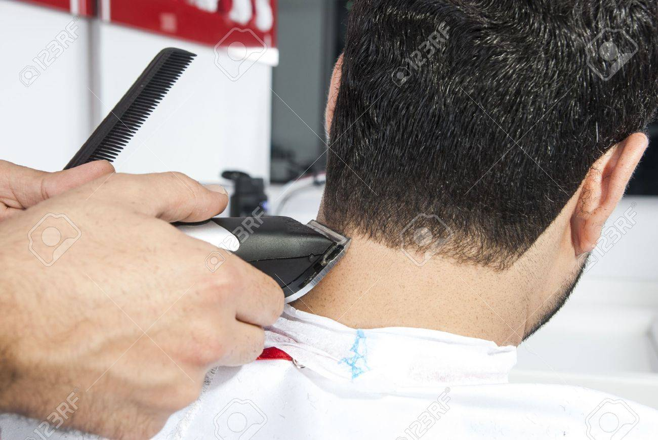 Barber Cutting Hair With Electric Razor At A Barber Shop Stock Photo