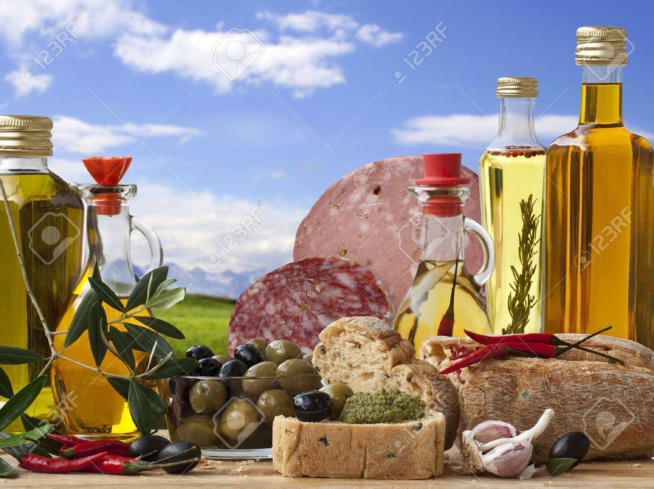 Decorative Italian deli with 5 different Olive Oil, Italian Bread, Italian Baloney and Salami, Olive and ingredient on a Landscape Background. Stock Photo - 7034998
