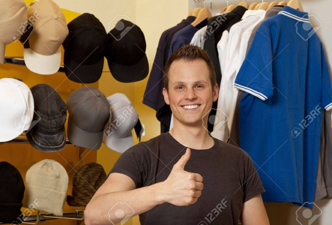 Young Man in her clothing store smiling and showing thumbs up Stock Photo - 12611458