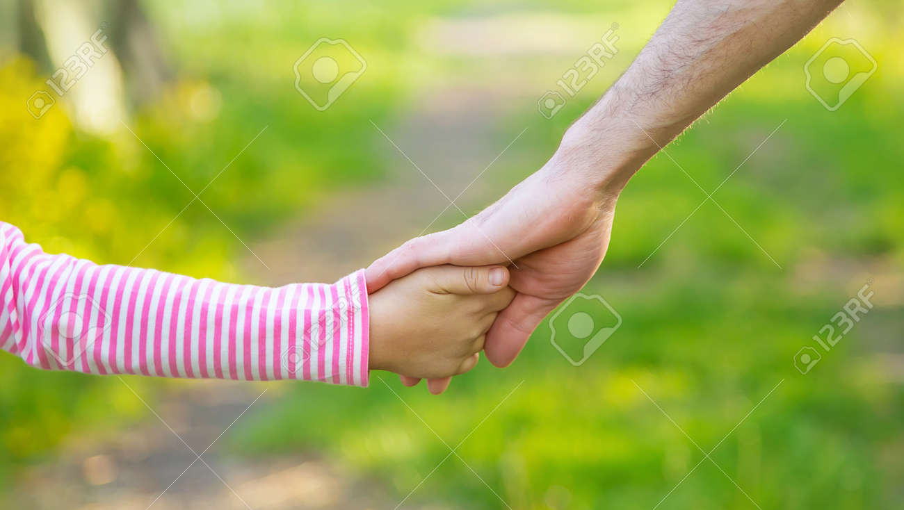A child with his father goes by the hand. Selective focus. nature. - 166694899