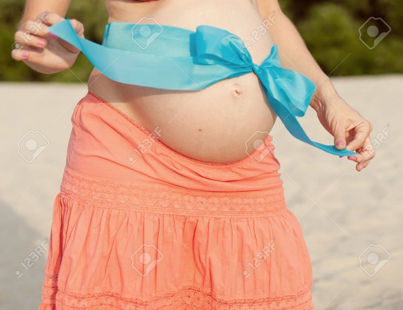 pregnant woman in a white dress with blue bow on her belly Stock Photo - 12677398