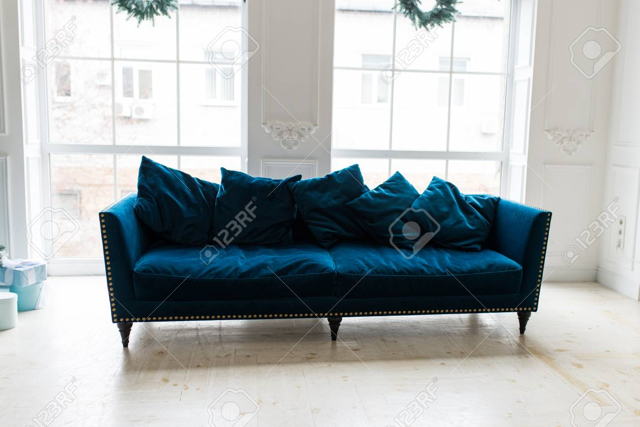 Blue sofa in white simple living room. Modern color of blue velvet..