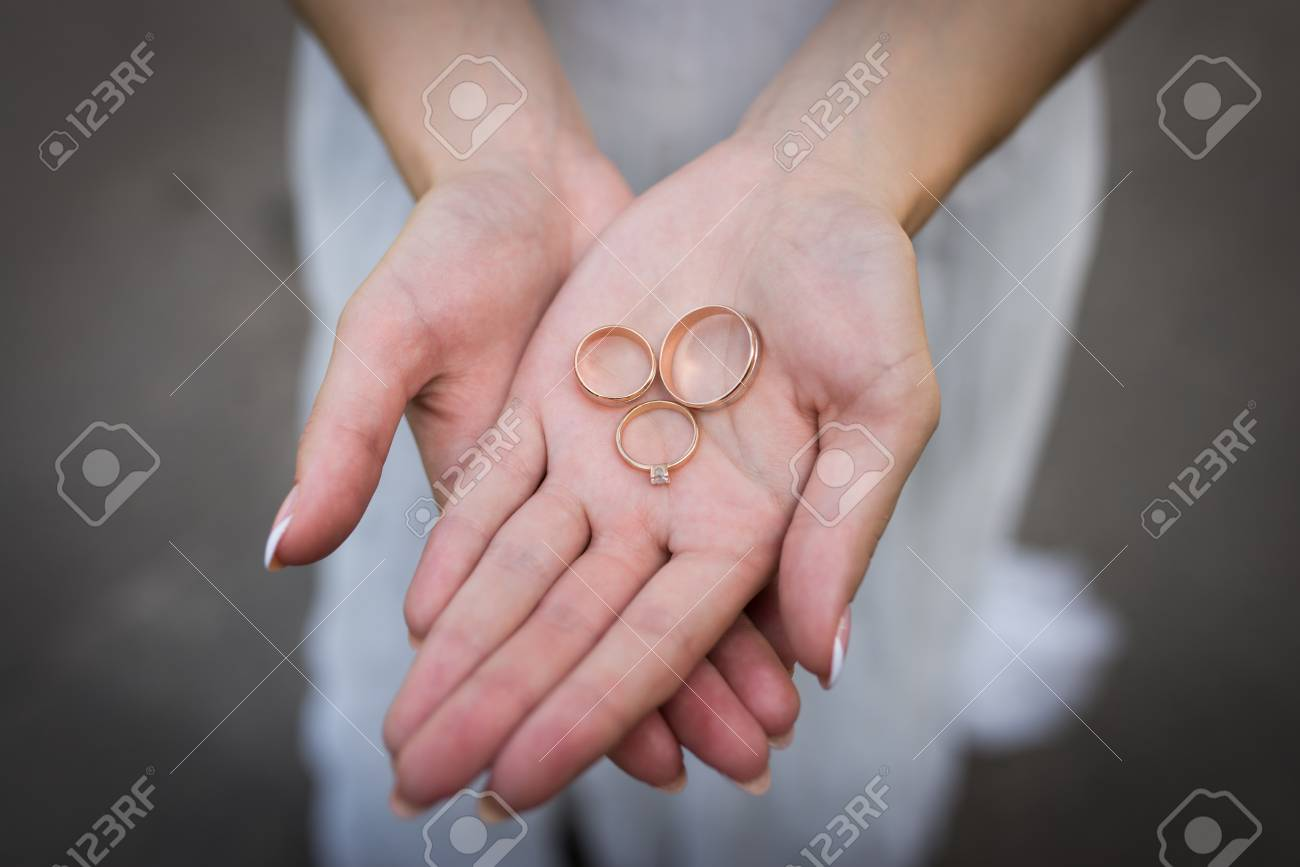 Two Golden Wedding Rings And An Engagement Ring With Diamond.. Stock ...