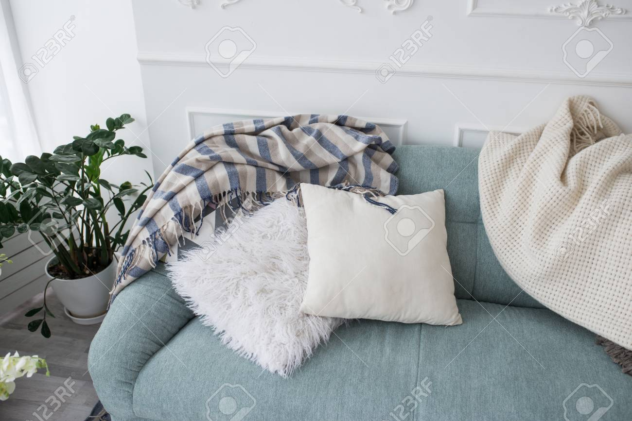 Two decorative pillows and bedspreads lie on a blue sofa. Cozy..