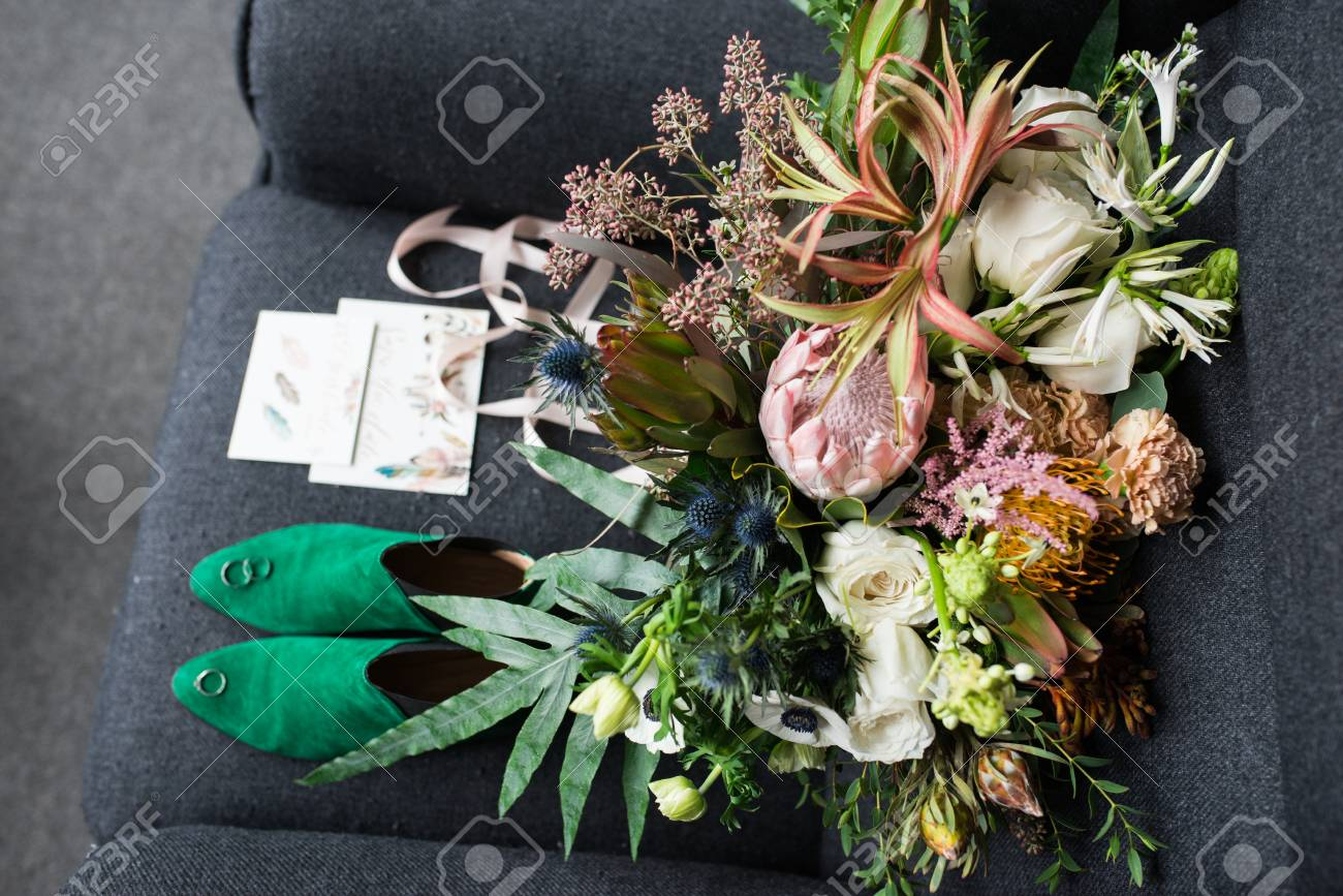 7ac8ffc8f90 Rich green wedding bouquet with pink ribbons on the gray armchair. Green  bridal shoes