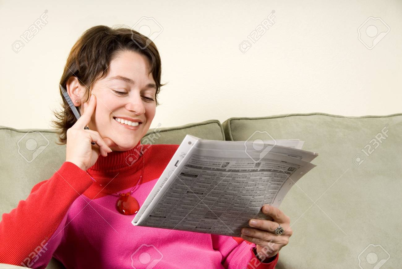 cute woamn reading the classifieds on couch Stock Photo - 621659