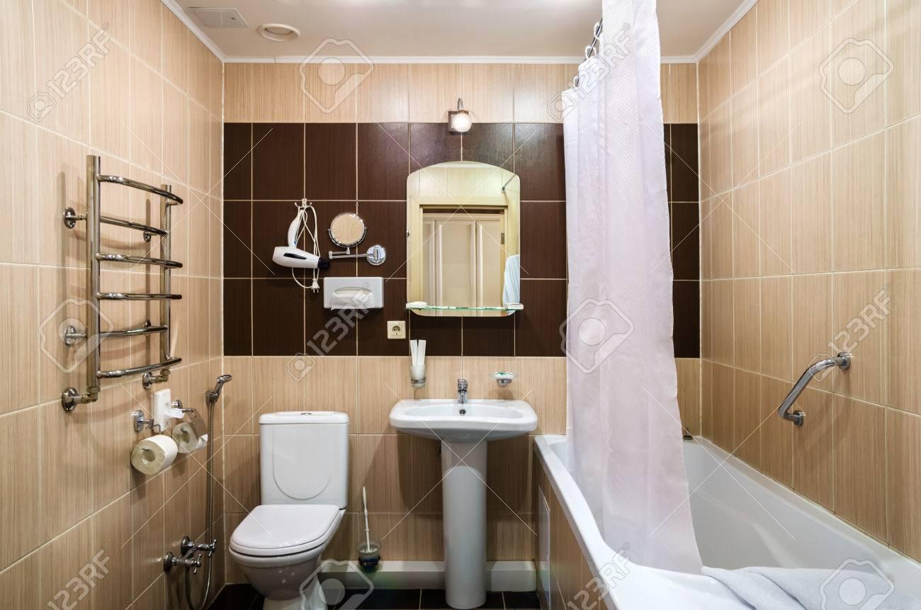 Bad in warmen farben mit wc badewanne haartrockner spiegel