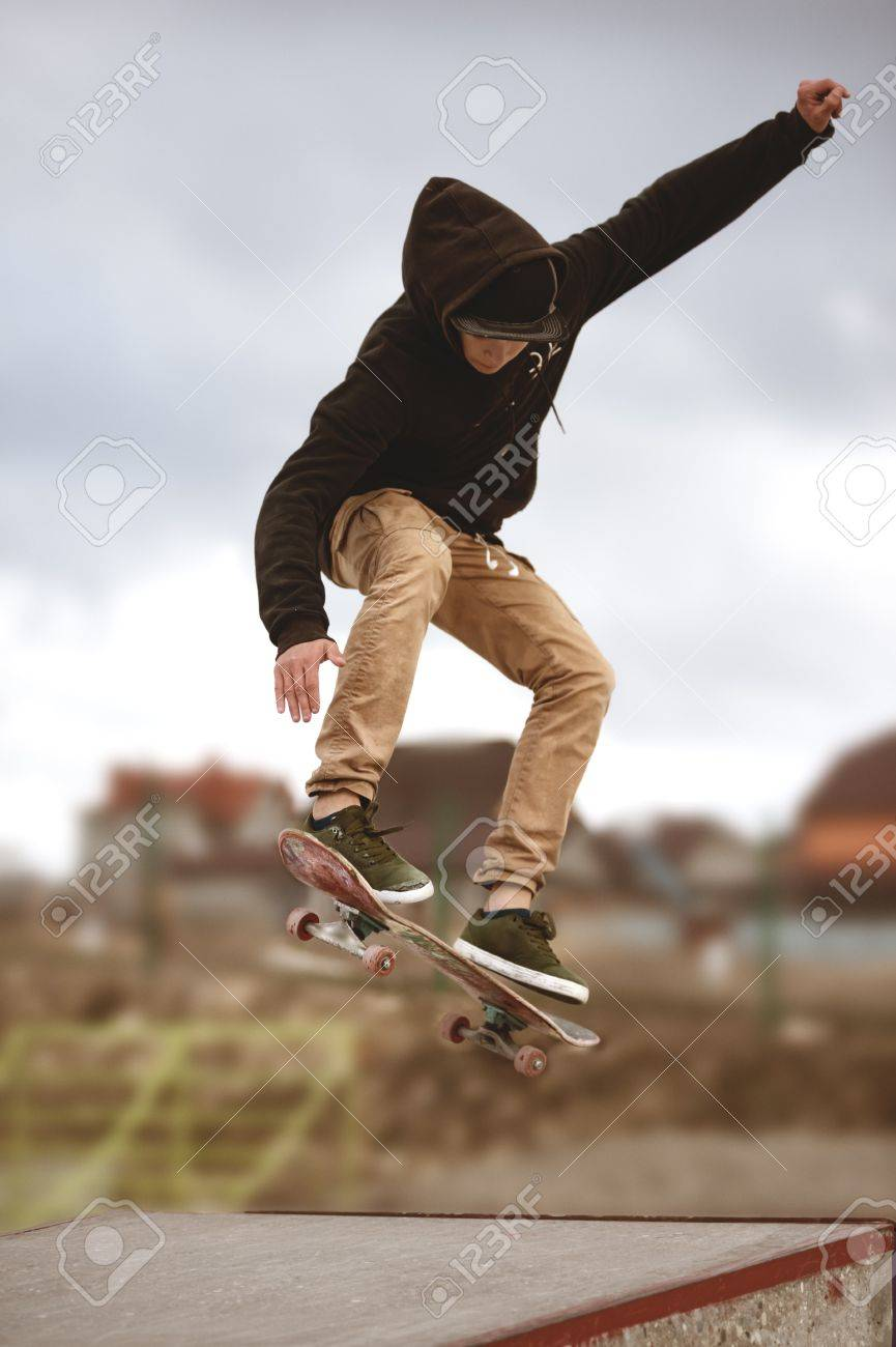 Close up of a skateboarders feet while skating active performance of stunt teenager shot in the air on a skateboard in a skate park - 74557219
