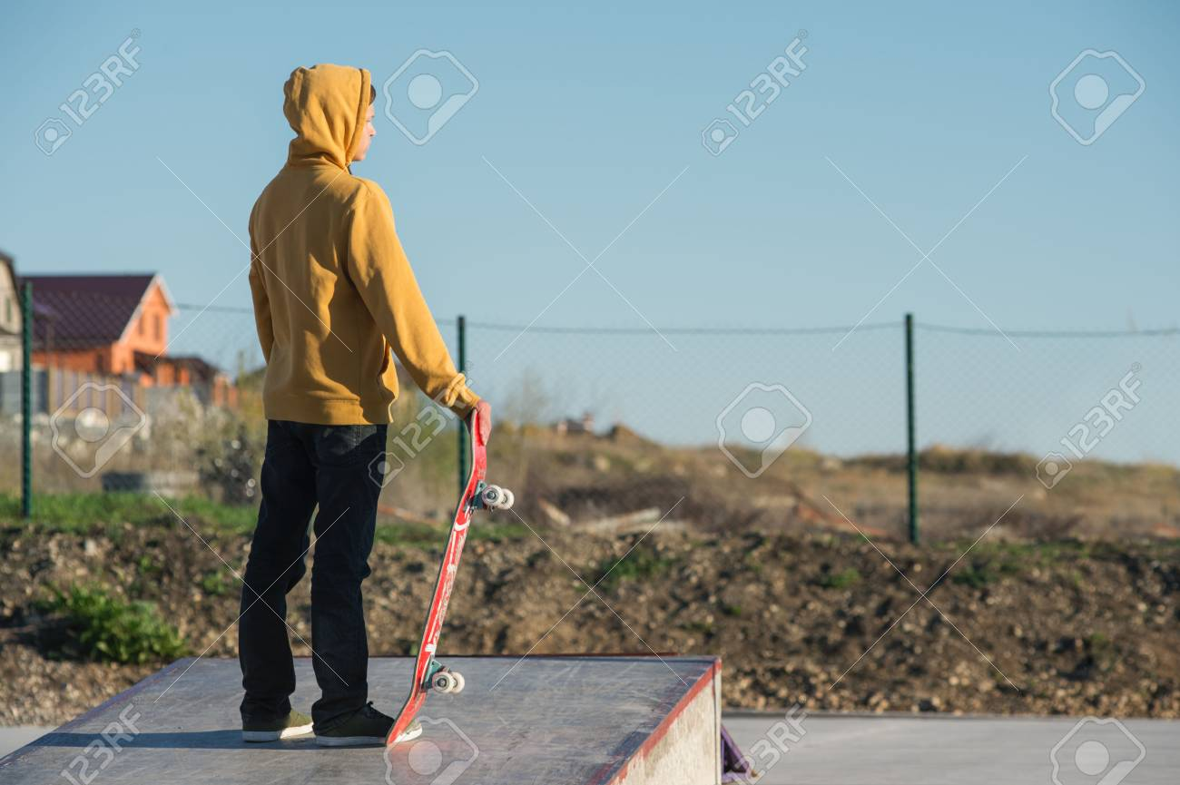 Teenager standing in a yellow hoodie holding a hand skateboard on the background urban slum - 77450362