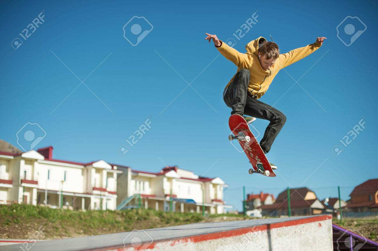 A teenager skateboarder does an ollie trick in a skatepark on the outskirts of the city - 77489878