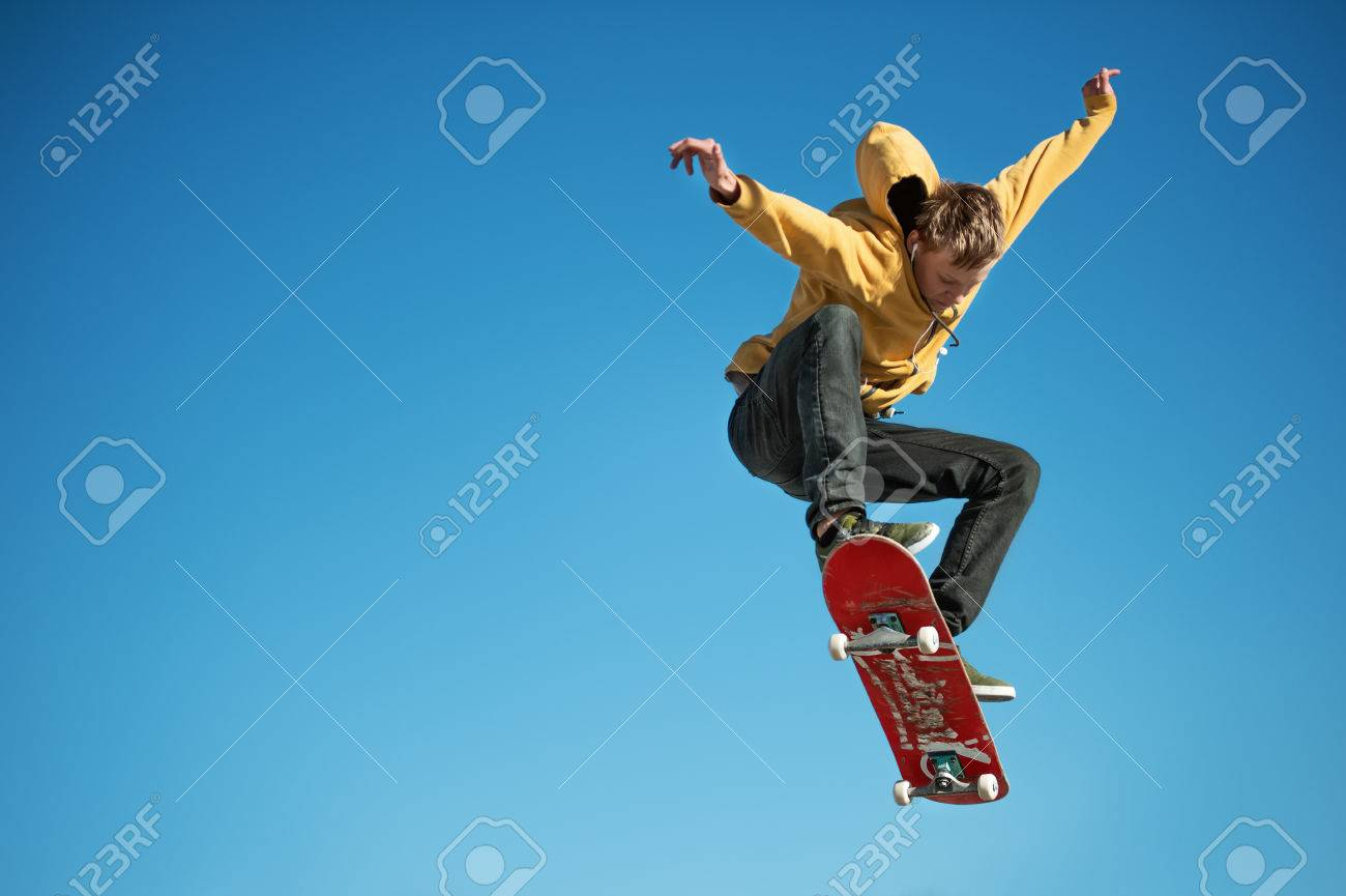 A teenager skateboarder does an ollie trick on background of blue sky gradient - 77490393