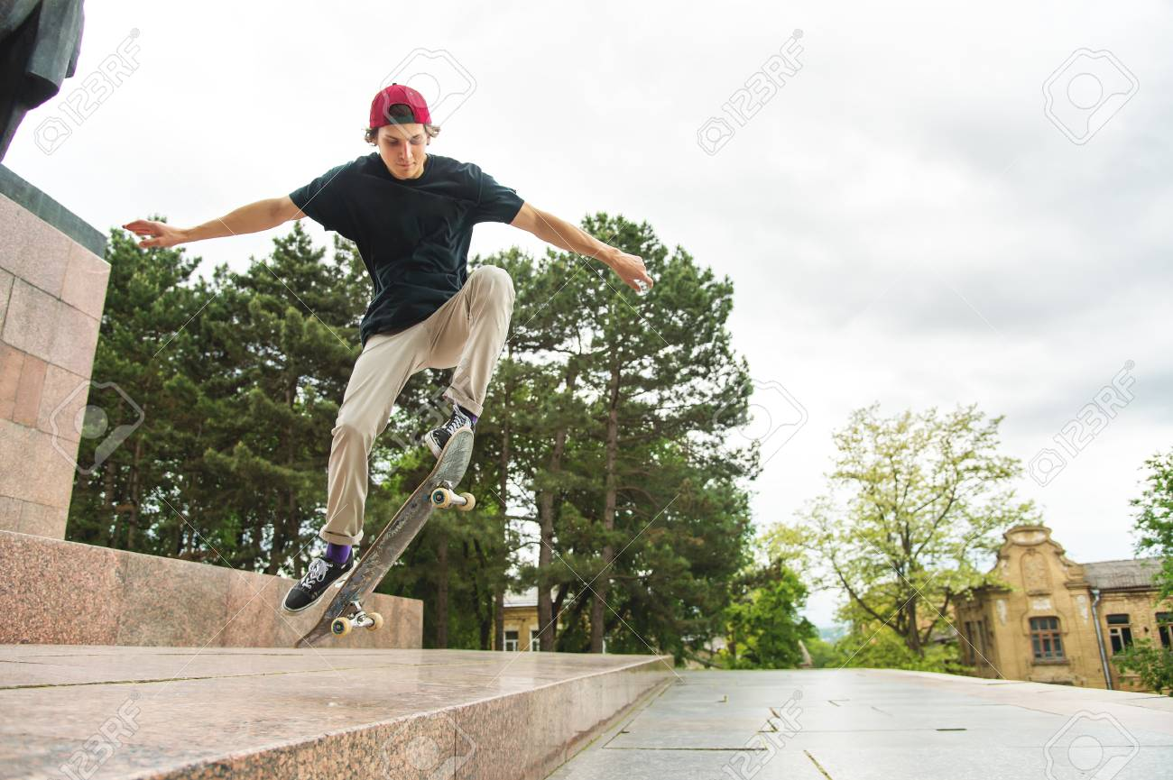 Long-haired skater-teenager in a T-shirt and a sneaker hat jumps an alley against a stormy sky - 82527981