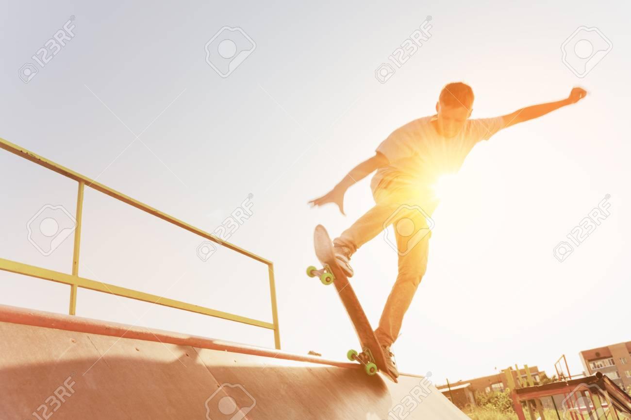 Teen skater hang up over a ramp on a skateboard in a skate park - 88328817