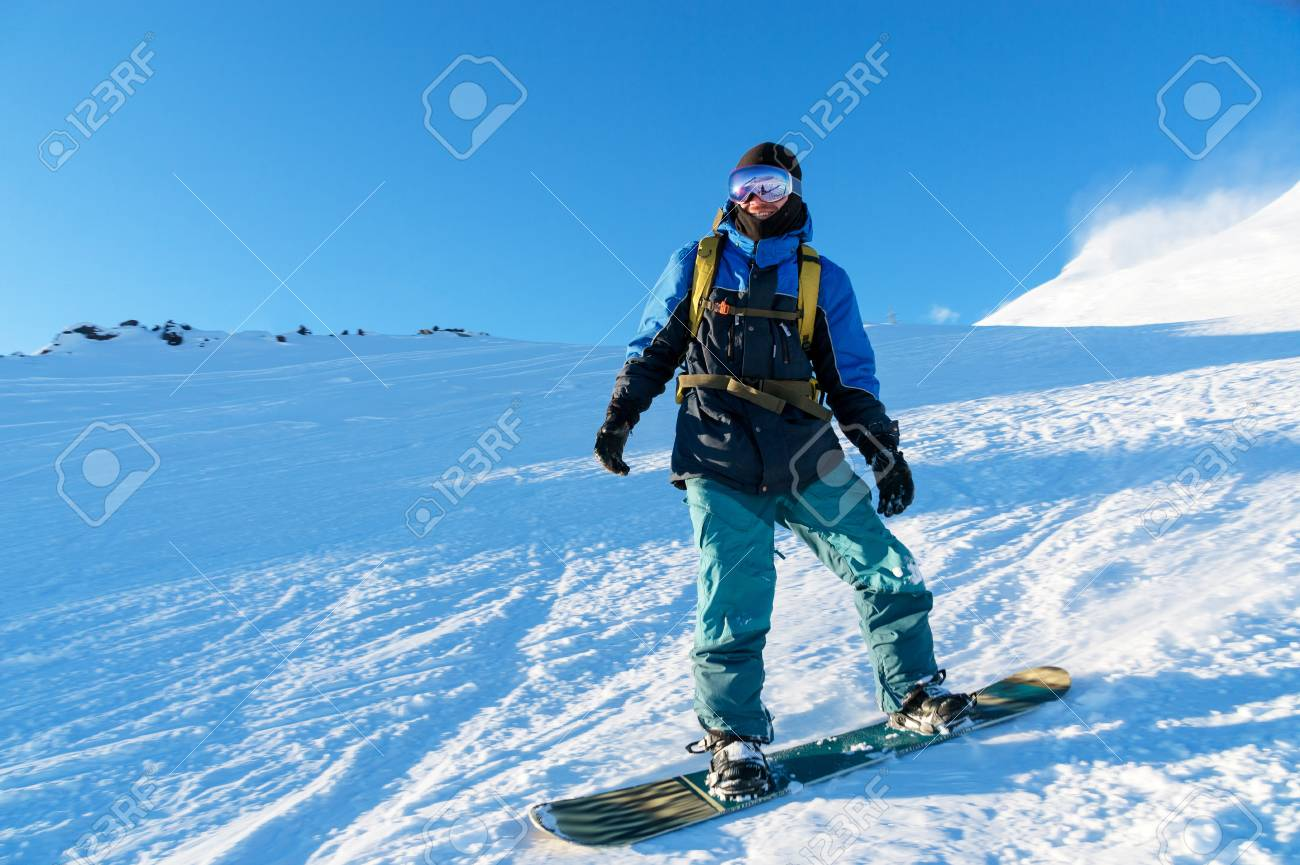 Freeride snowboarder rolls on a snow-covered slope leaving behind a snow powder against the blue sky - 91272321