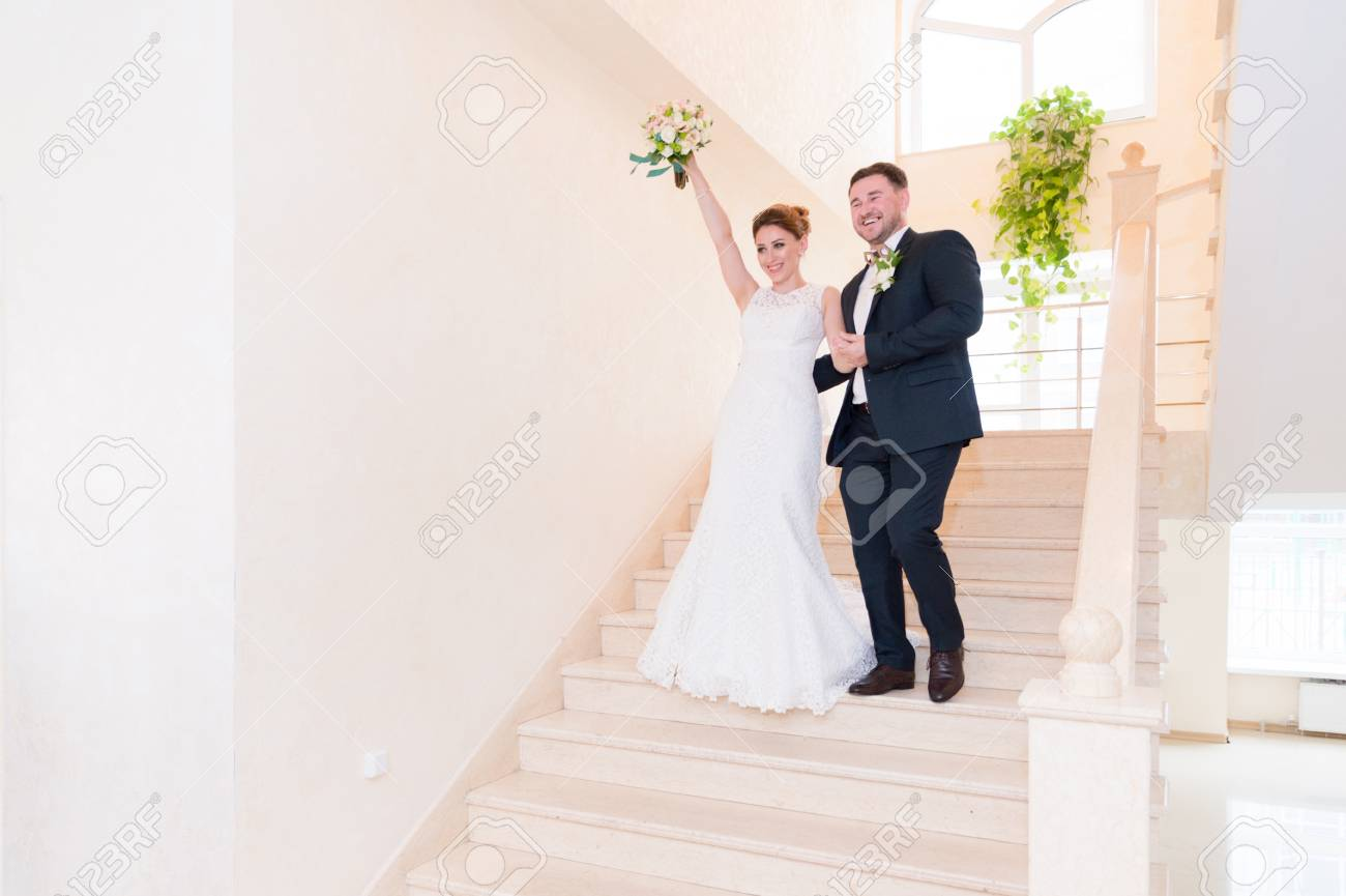 A Couple Of Newlyweds Go Down The Stairs In The Registry Office