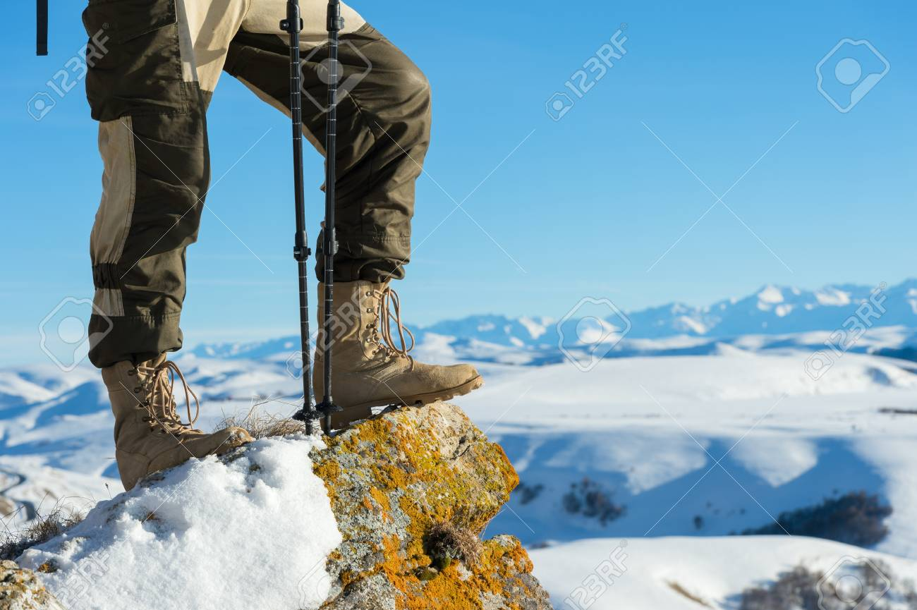 Close Up Of A Tourists Foot In Trekking Boots With Sticks For