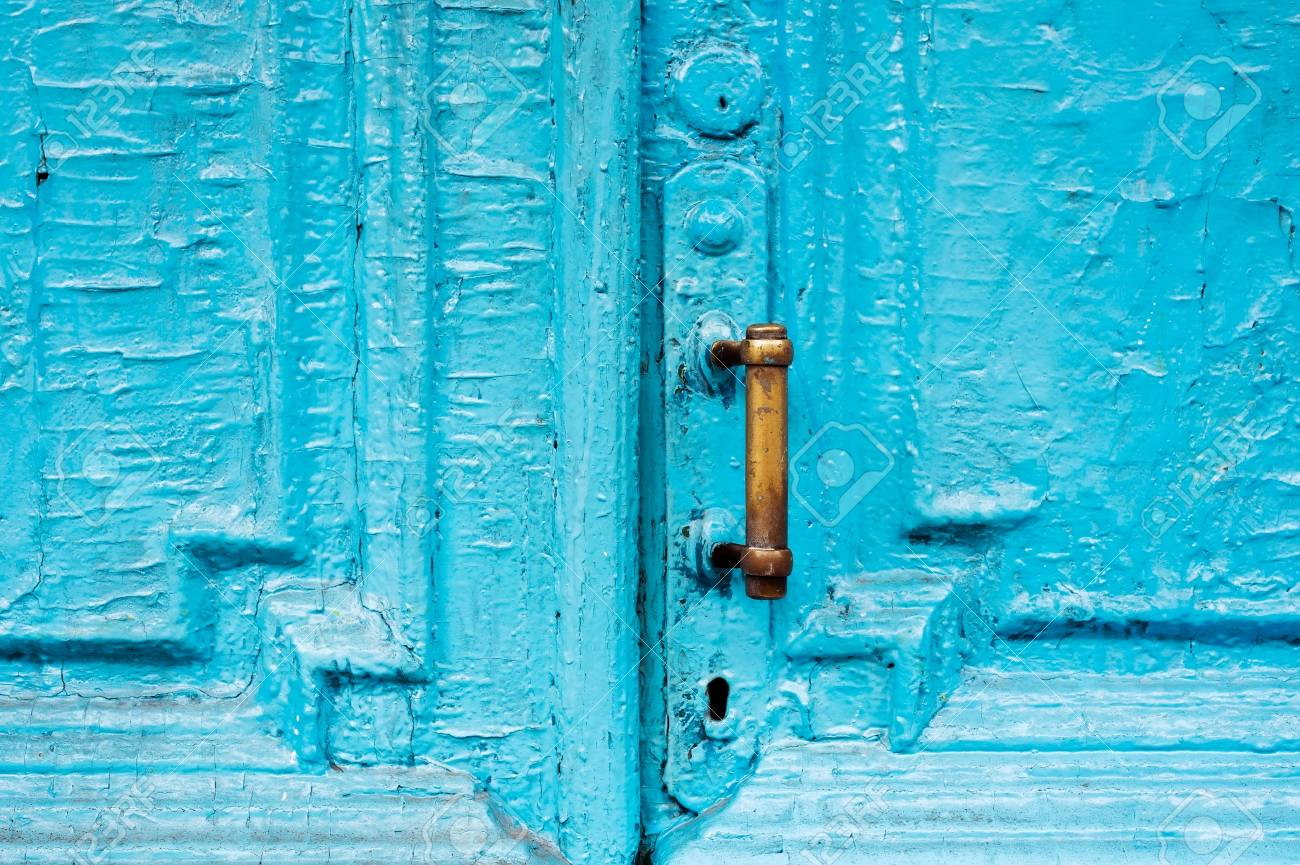 Close-up keyholes with curtains and a handle on the blue many times painted cracked double-barreled wooden vintage door of the last century with a post slit. - 95804251